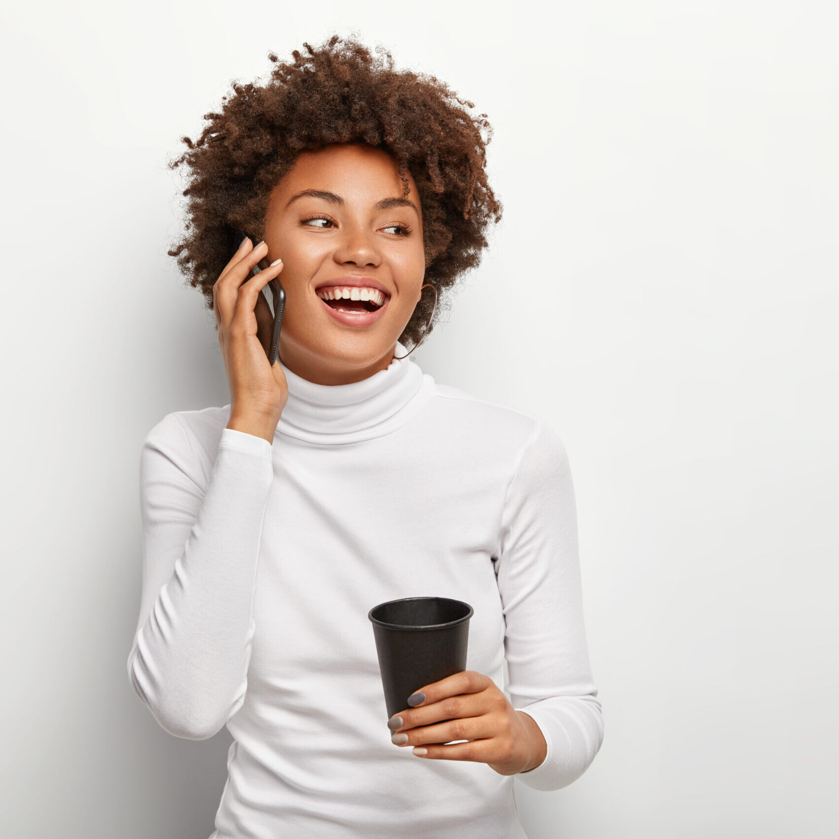 Photo of satisfied carefree woman with curly haircut, talks via smartphone, looks positively aside, drinks takeout coffee, being in good mood during lively conversation. People and lifestyle